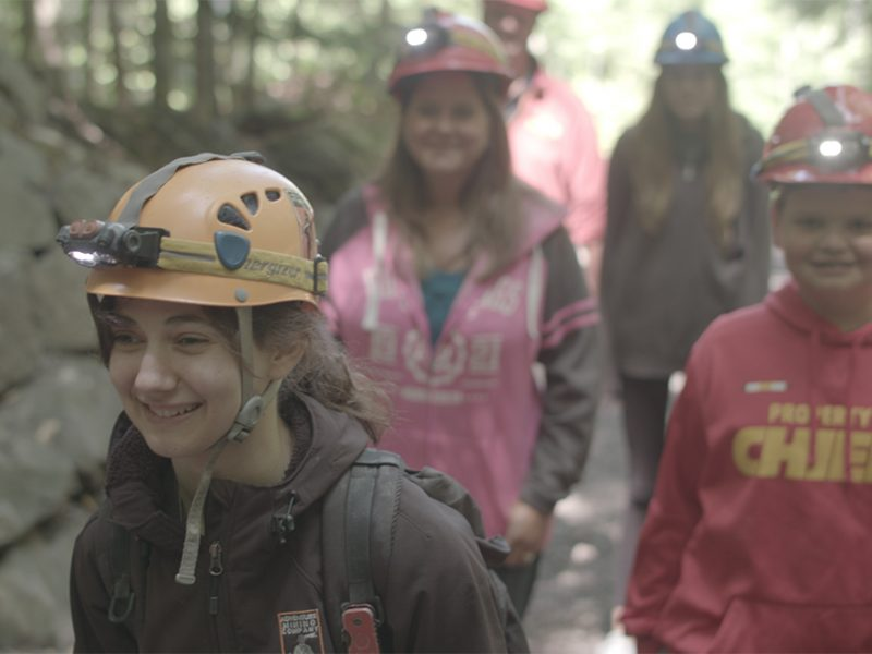 Guide-Leading-Group-into-the-Adventure-Mine-Smiling