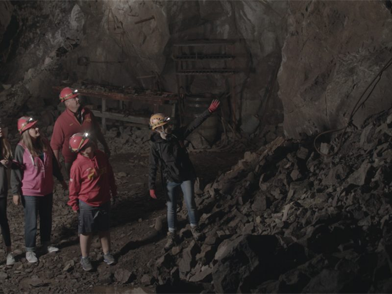 Tour-Guide-Pointing-at-Features-Underground-in-the-Adventure-Mine